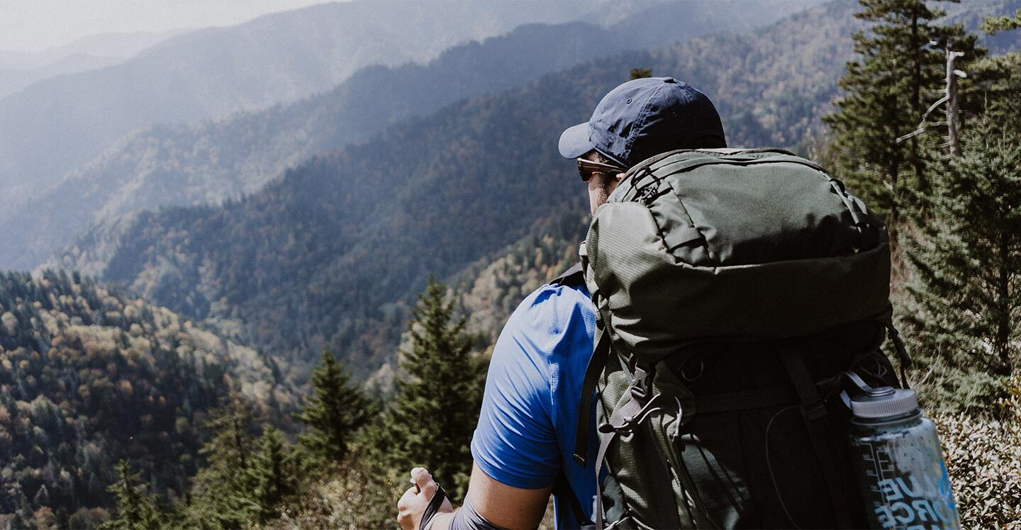 man with a hiking backpack on talking through the woods during daytime