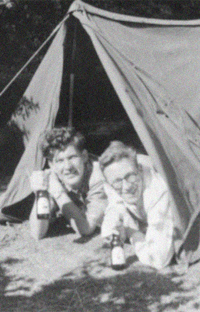 vintage black and white photo of two people under a tent holding beer bottles