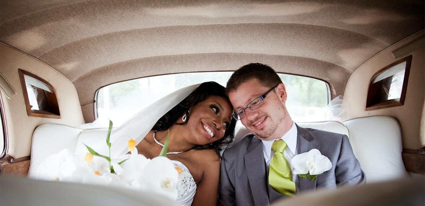 bride and groom sitting in the backseat of a limo leaning on each other and smiling