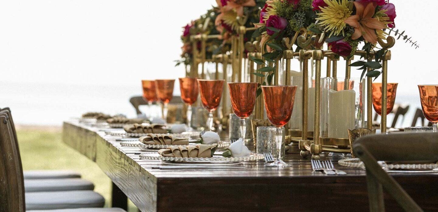 large wooden outdoor dining table with a long floral centrepiece and place settings