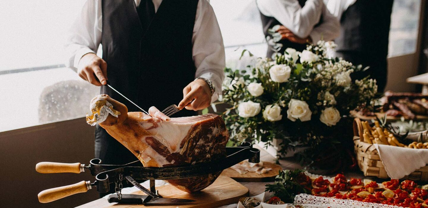 server slicing into a large prosciutto at a buffet table covered in a variety of hors d'oeuvres