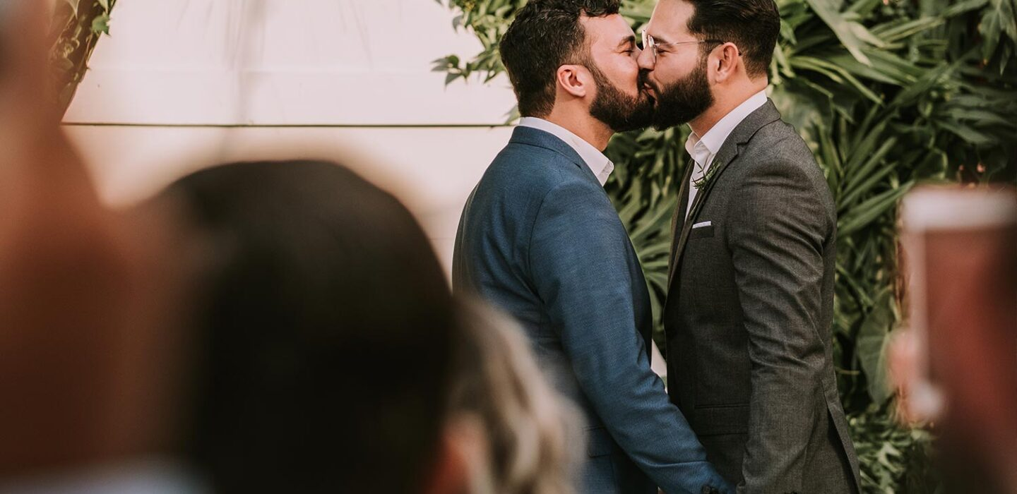 two grooms kissing at the alter