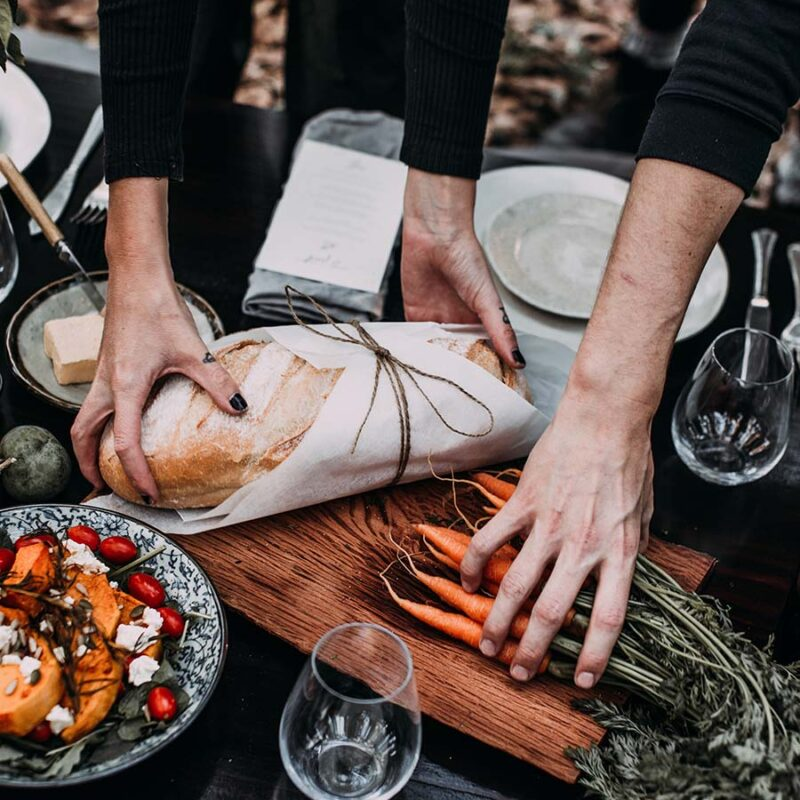 people placing a loaf of bread and bunch of carrots onto a dining table