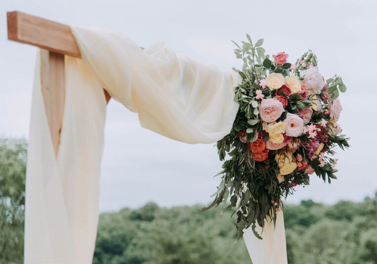 flower bouquet tied around the right corner of large wooden wedding arbor in outdoor venue