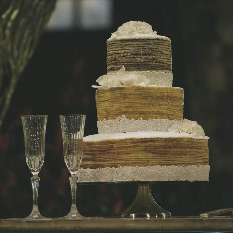 rustic three tiered wedding cake on wooden stand next to two champagne glasses