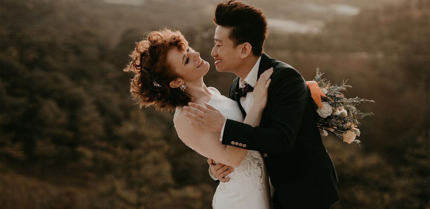 bride and groom embrace overlooking skyline off of mountain top