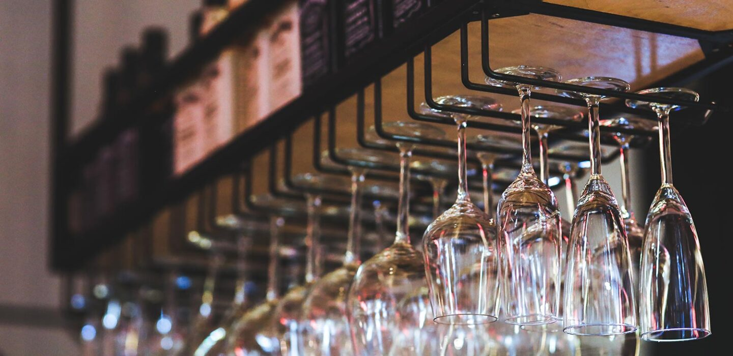 hanging clear glasses at a bar with whisky bottles displayed above them