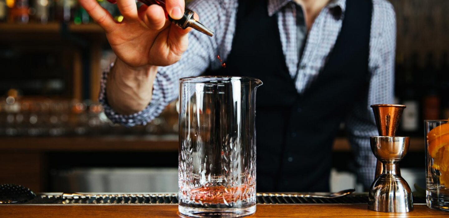 bartender pouring a drink from a small bottle into a large clear glass at the bar