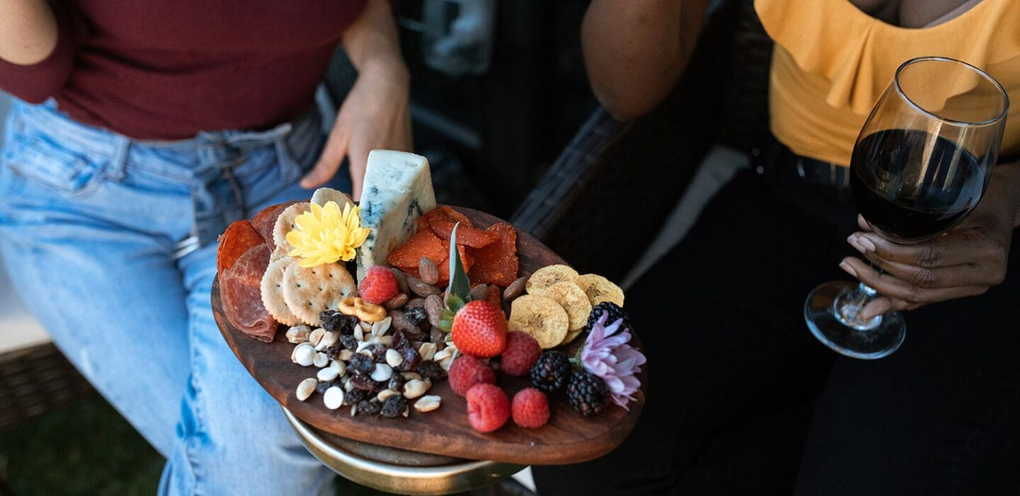 two women holding fruit, nut, crackers, cheese and dried meats on a wooden platter