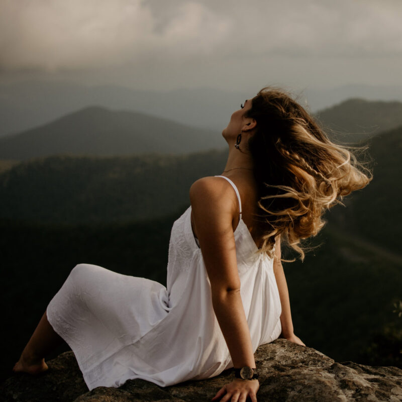 woman sitting on top of a rock leaning back on her hands with the wind blowing her hair