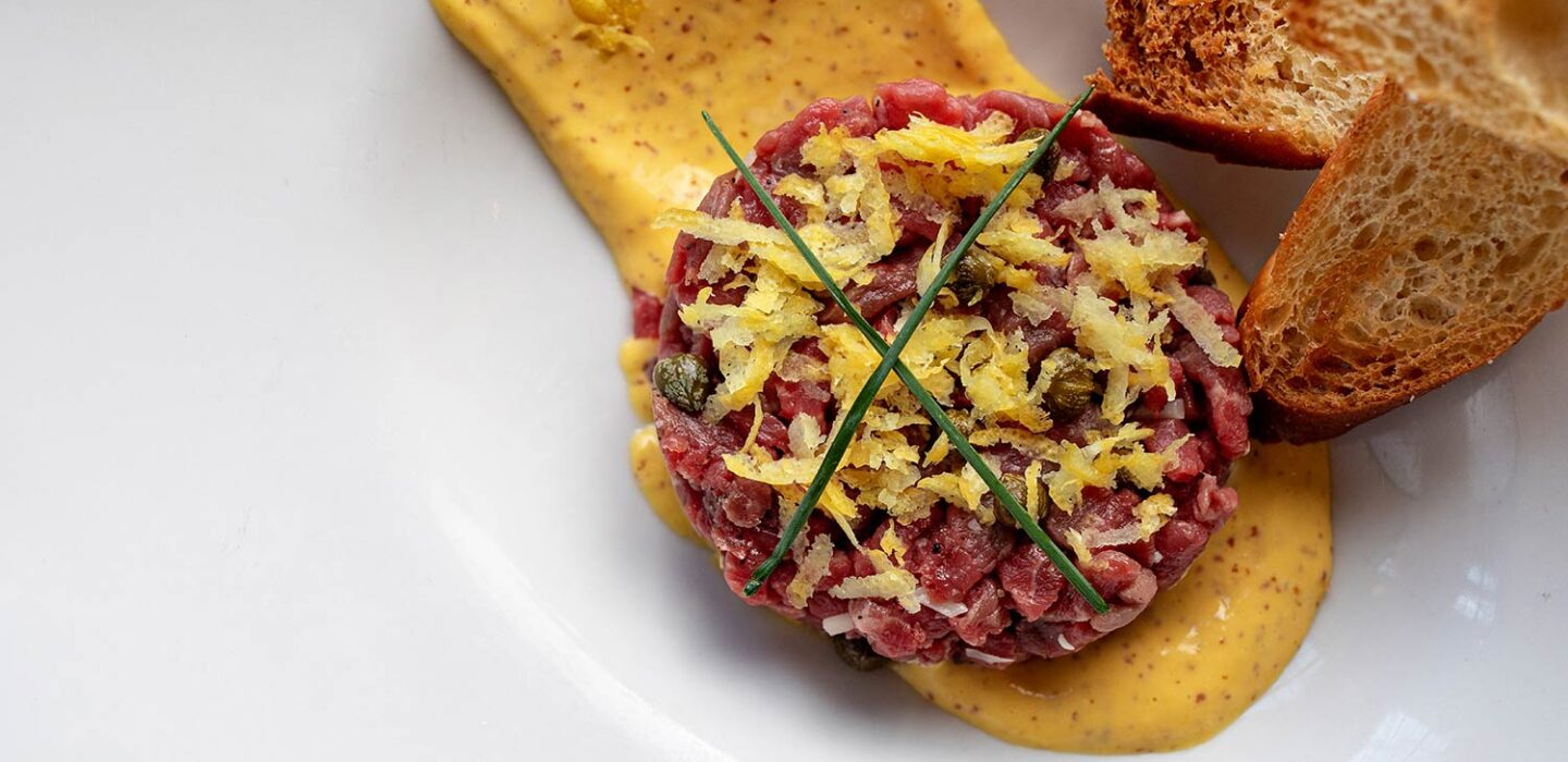 steak tartare on a yellow sauce in a plate with two slices of toasted bread