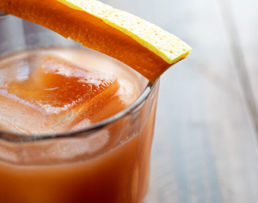 close up of an orange cocktail with a large icecube inside and an orange slice garnish