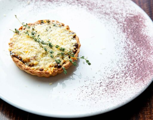 baked pie on a ceramic plate garnished with greens