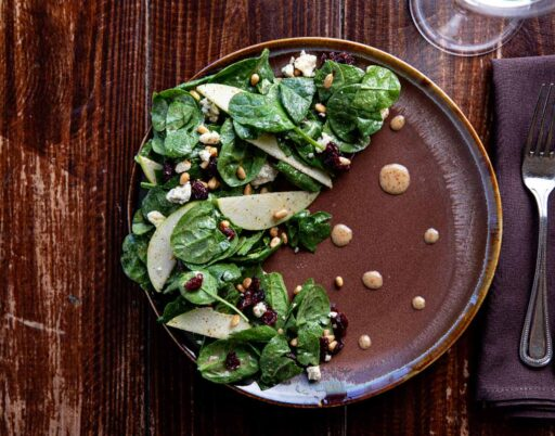 salad dish with apple slices, seeds, and cranberries on a wooden table