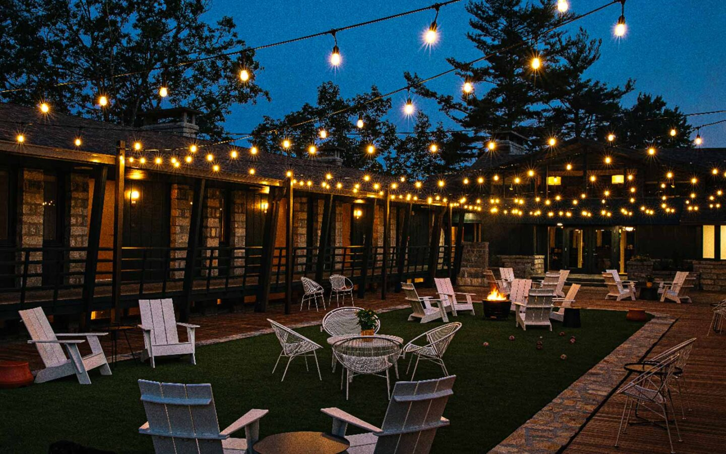 outdoor seating area for events at night time with outdoor furniture and lights