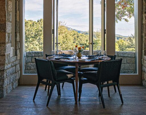 dining table and chairs in an industrial style dining room with large windows overlooking the forest