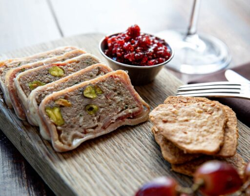 stuffed meat dish on a wooden platter with cranberries and crackers