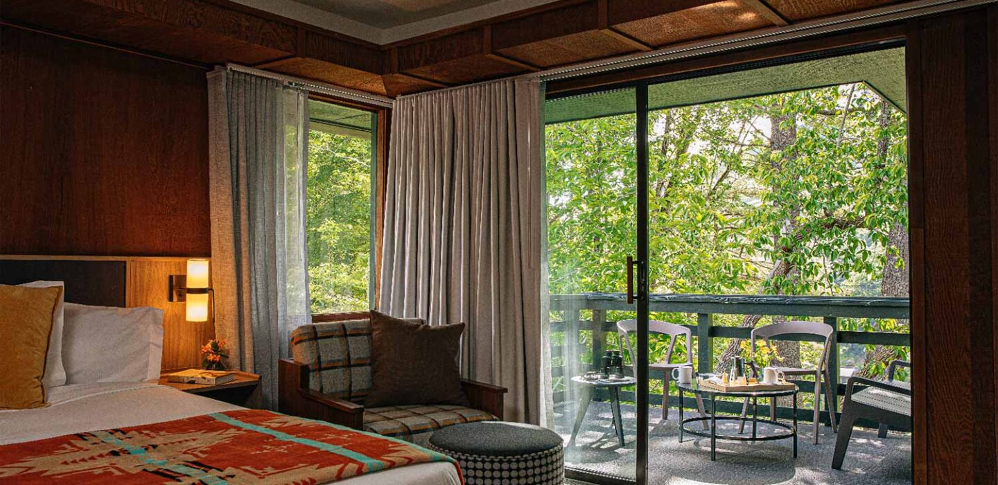 lodge guest room with a large bed, reading seat, and large windows with balcony and forest view
