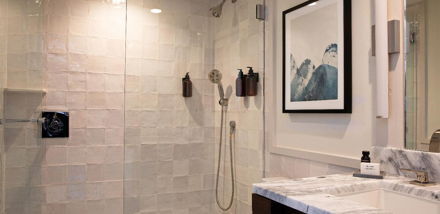white bathroom with a glass door shower and marble vanity